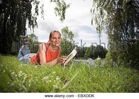 Frau liegt auf der Wiese in einem Park, ein Buch zu lesen - Stockfoto