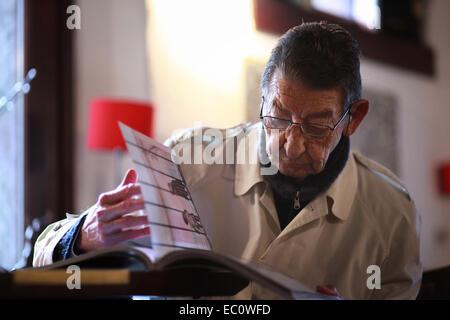 Porträt von einem italienischen Senioren sitzen in einer Weinbar, versenkt in einem Buch der Fotografie. Spilimbergo, - Stockfoto
