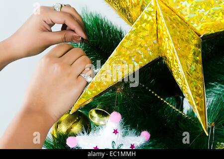 ein Mädchen Weihnachtsbaum binden Geschenk - Stockfoto
