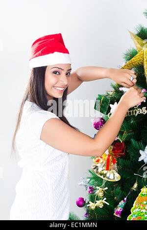 ein indisches Mädchen Weihnachtsbaum binden Geschenk - Stockfoto