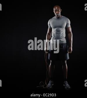 Studio shot der Fit und muskulöser Mann mit springen Seil stehend auf schwarzem Hintergrund. Afroamerikanische Männermodel - Stockfoto
