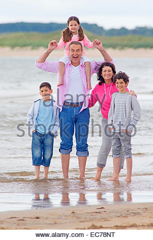Großeltern und Enkelkinder lächelnd am Strand - Stockfoto