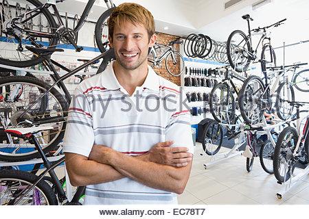 Filialleiter in Fahrradgeschäft lächelnd in die Kamera - Stockfoto