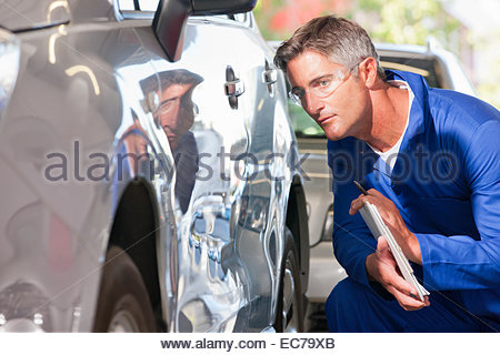 Mechaniker, die Inspektion beschädigten Fahrzeugs - Stockfoto