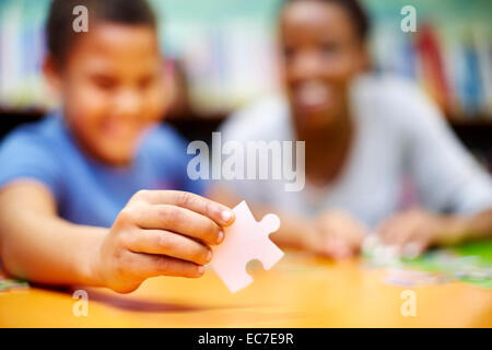 Junge Frau und junge tut eine Puzzle in Bibliothek - Stockfoto