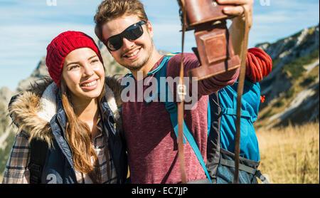 Österreich, Tirol, Tannheimer Tal, junges Paar, Selbstportrait mit altmodischen Kamera - Stockfoto