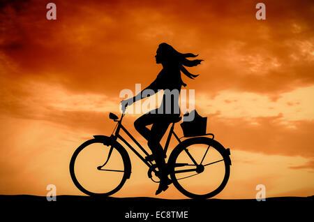 Ein Mädchen auf dem Fahrrad bei Sonnenuntergang - Stockfoto