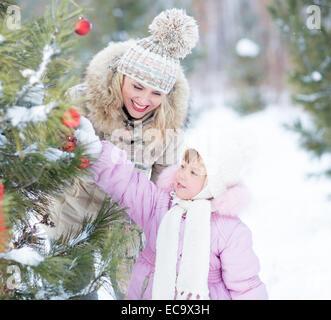 Glückliche Familie Mutter und Kind spielt mit Weihnachtsbaum Dekoration im freien - Stockfoto