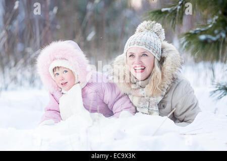 Glückliche Familie Mutter und Tochter spielen mit Schnee im Winter im freien - Stockfoto