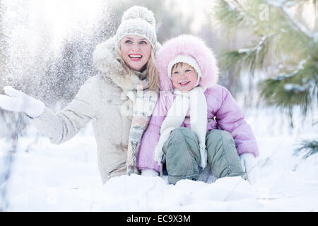 Glückliche Familie Mutter und Tochter sitzen im Schnee im Winter - Stockfoto