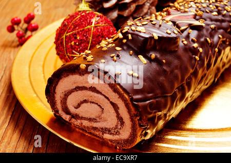Nahaufnahme eines Kuchens Yule Log, traditionelle Weihnachtszeit in einem goldenen Tablett auf einem rustikalen - Stockfoto