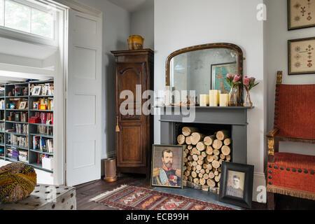 Vintage Teppich auf Holzboden Kamin mit Protokollen und Familienportraits - Stockfoto
