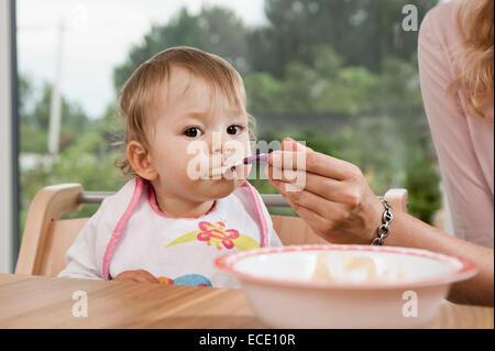 Mutter, Fütterung 1 Jahr altes Babymädchen Essen - Stockfoto