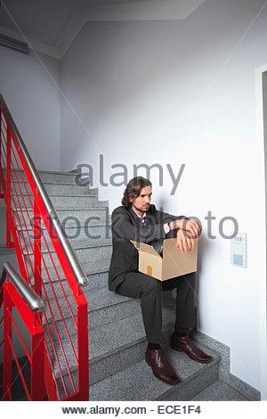 Junger Mann sitzen Schritte Arbeitslosen allein gedrückt - Stockfoto