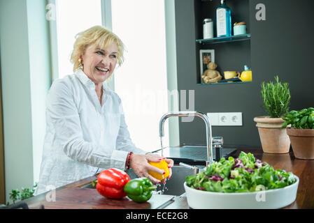 Ältere Frau waschen Kochen Küche - Stockfoto