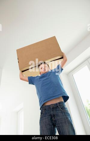Jungen tragen schwere Kiste neues Zimmer Haus - Stockfoto