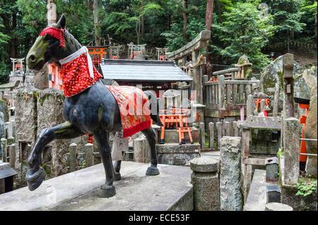 Kyoto, Japan. Ein Shinto-Friedhof am Berghang am Schrein des Fushimi Inari-Taisha. Statue der Heiligen Pferde - Stockfoto