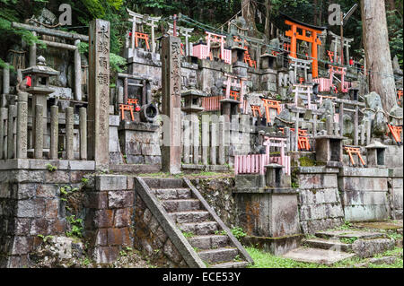 Kyoto, Japan. Ein Shinto-Friedhof am Berghang am Schrein des Fushimi Inari-Taisha, mit vielen kleinen Torii-Tore - Stockfoto