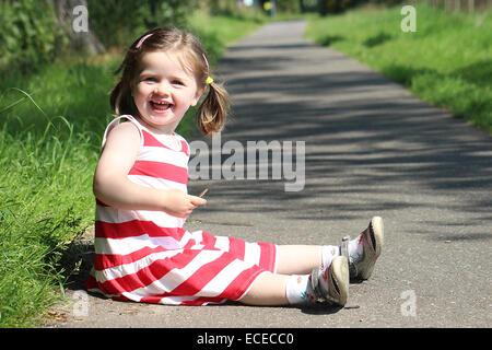 Kleines Mädchen sitzt auf Fußweg und lächelnd - Stockfoto