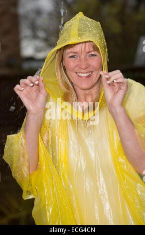 Tragen einen Plastiken Poncho während einer Dusche Regen lachende Frau - Stockfoto