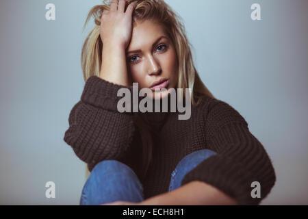 Bild der schönen weiblichen Modell tragen Pullover mit der Hand im Haar. Studioaufnahme von attraktiven Frau. - Stockfoto