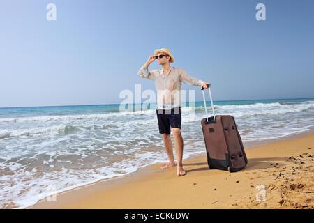 Junge Touristen mit seinem Gepäck an einem Sandstrand am Meer verloren - Stockfoto