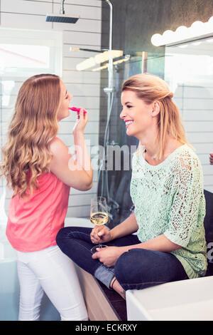 Lächelnde junge Frau sitzt von Schwester Auftragen von Lippenstift im Badezimmer - Stockfoto