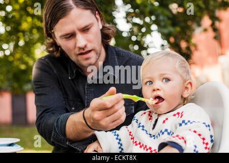 Junger Mann Fütterung Babymädchen im park - Stockfoto