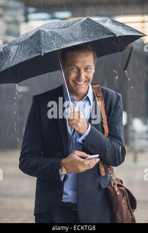 Porträt von lächelnden Geschäftsmann mit Smartphone in der Stadt während der Regenzeit - Stockfoto