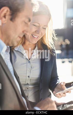 Geschäftsleute, die Benutzung von Mobiltelefonen im freien - Stockfoto