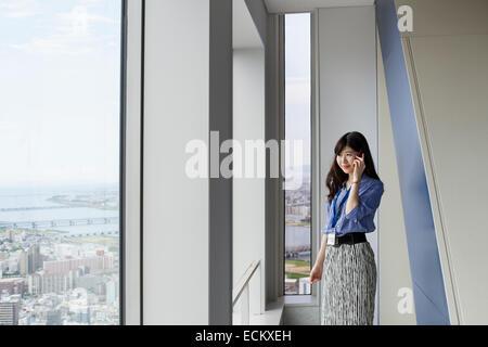 Eine berufstätige Frau in einem Bürogebäude. - Stockfoto