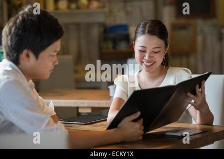 Frau und Mann sitzt an einem Tisch in einem Café, Blick auf die Speisekarte, lächelnd. - Stockfoto