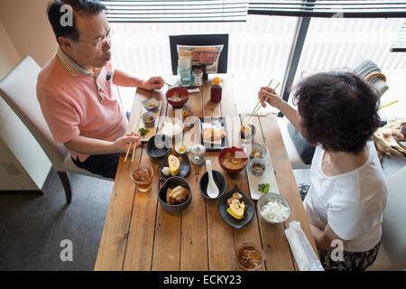 Frau und Mann sitzt an einem Tisch, japanisches Essen mit Stäbchen zu essen.