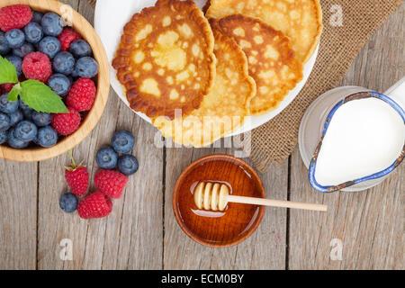 Pfannkuchen mit Himbeeren, Heidelbeeren, Milch und Honig Sirup. Auf Holztisch - Stockfoto