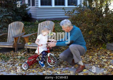 Großvater lehrt seine Enkelin ein Dreirad fahren - Stockfoto