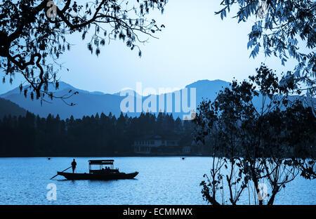 Traditionelle chinesische hölzerne Freizeit Boot schwimmt auf das Stille Wasser. Wandern rund um den berühmten Park - Stockfoto