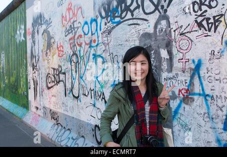 Berlin Deutschland verbliebenen Teil der Berliner Mauer mit chinesischen Touristen mit Künstler Malerei in Innenstadt - Stockfoto