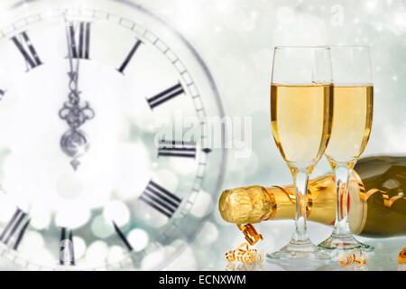 Flaschen und Gläser mit Champagner gegen Weihnachtslichter und Uhr kurz vor Mitternacht - Stockfoto
