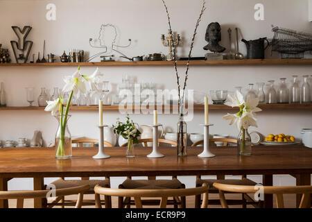 Lilien und Kerzen auf große Bauernhaus Esstisch mit Holzstühlen im stilvollen Speisesaal mit offenen Regalen - Stockfoto