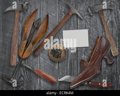 Vintage Damen-Schuh und Schuhmacher-Tools über Holztisch, Platz für Ihren Text auf eine leere Visitenkarte - Stockfoto
