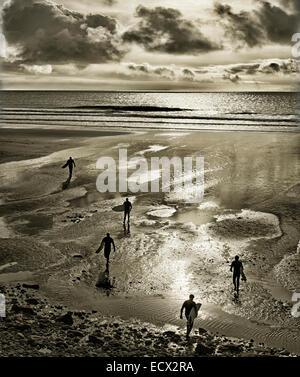 Silhouetten von Surfern zu Fuß mit Surfbrettern auf Perranuthnoe Strand - Stockfoto