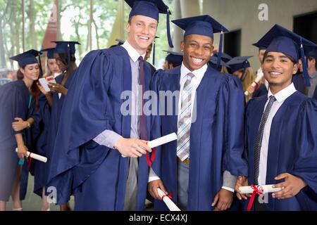 Porträt von drei männliche Studenten in Graduierung Kleider halten Diplome lächelnd - Stockfoto