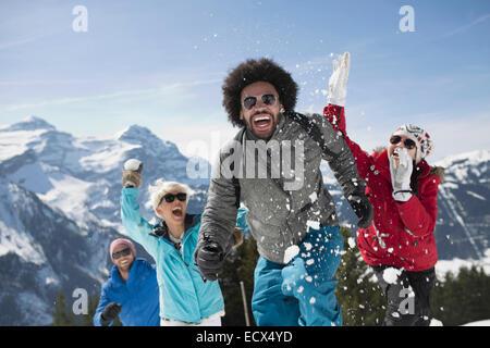 Freunde genießen Schneeballschlacht am Berg - Stockfoto