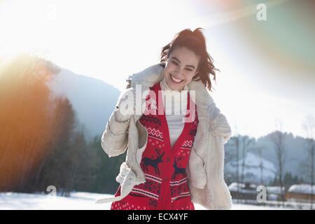 Lächelnde Frau in schneebedecktes Feld - Stockfoto
