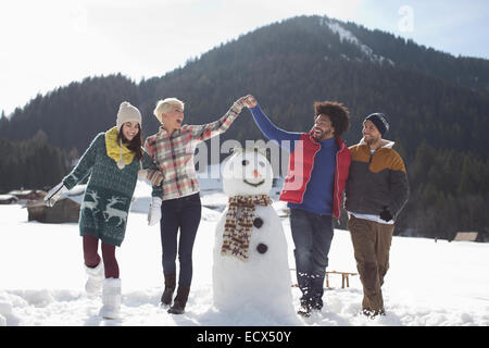 Freunde Herumspielen Schneemann - Stockfoto