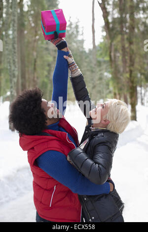 Paar für Weihnachtsgeschenk im Schnee zu erreichen - Stockfoto