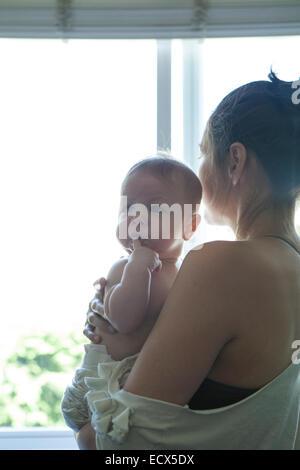 Mutter Baby halten und Blick durch Fenster - Stockfoto