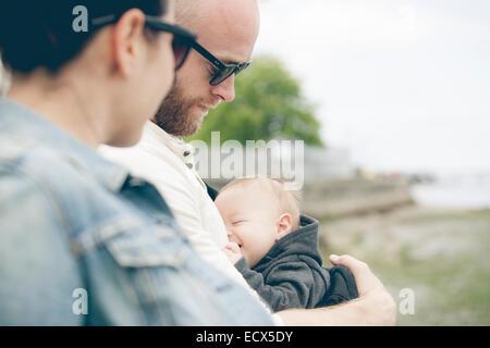 Eltern tragen Sonnenbrillen halten kleine baby im freien - Stockfoto