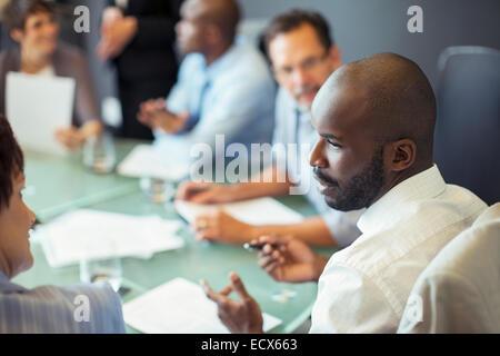 Unternehmer im Gespräch mit Kollegen während Geschäftstreffen im Konferenzraum - Stockfoto