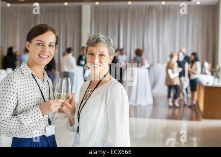 Zwei Geschäftsfrauen mit Champagner-Flöten in Händen, Kolleginnen und Kollegen im Hintergrund stehend - Stockfoto